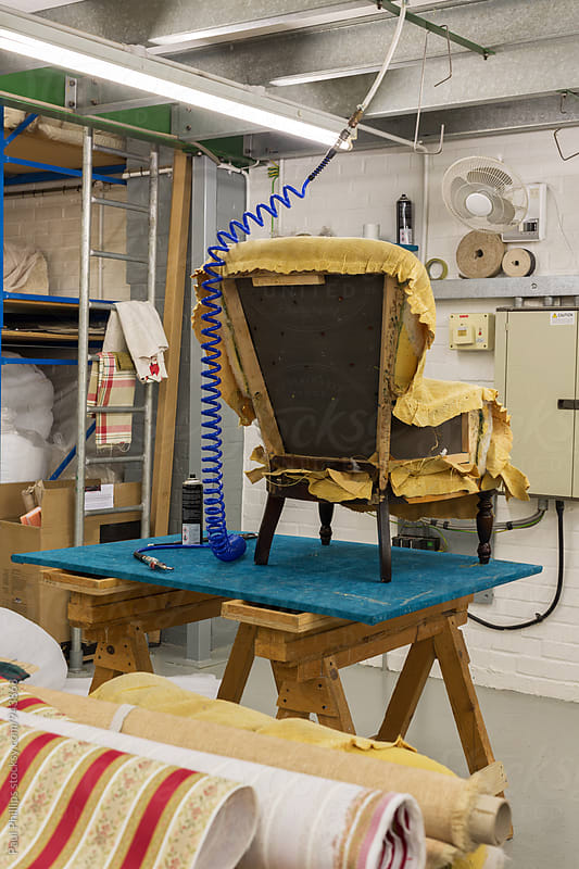 Chair undergoing renovation standing on a bench in an upholstery workshop. by Paul Phillips for Stocksy United
