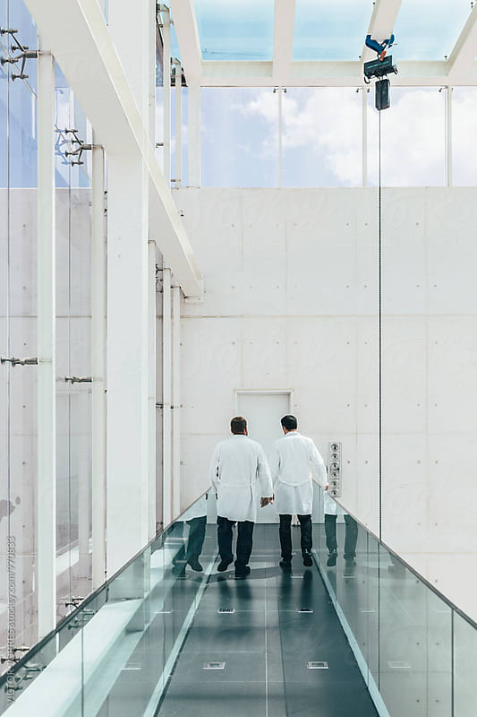 Doctors Walking Through a Modern Hospital Corridor by Victor Torres for Stocksy United