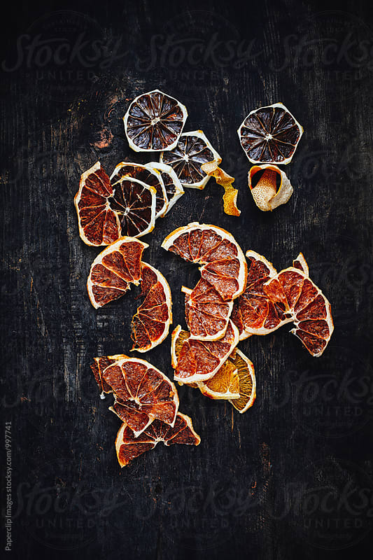 Dried orange slices on dark wooden table. by Paperclip Images for Stocksy United