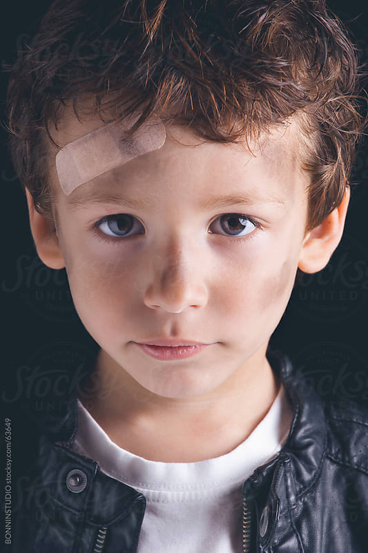 Child with band aid looking camera on black background. by BONNINSTUDIO for Stocksy United