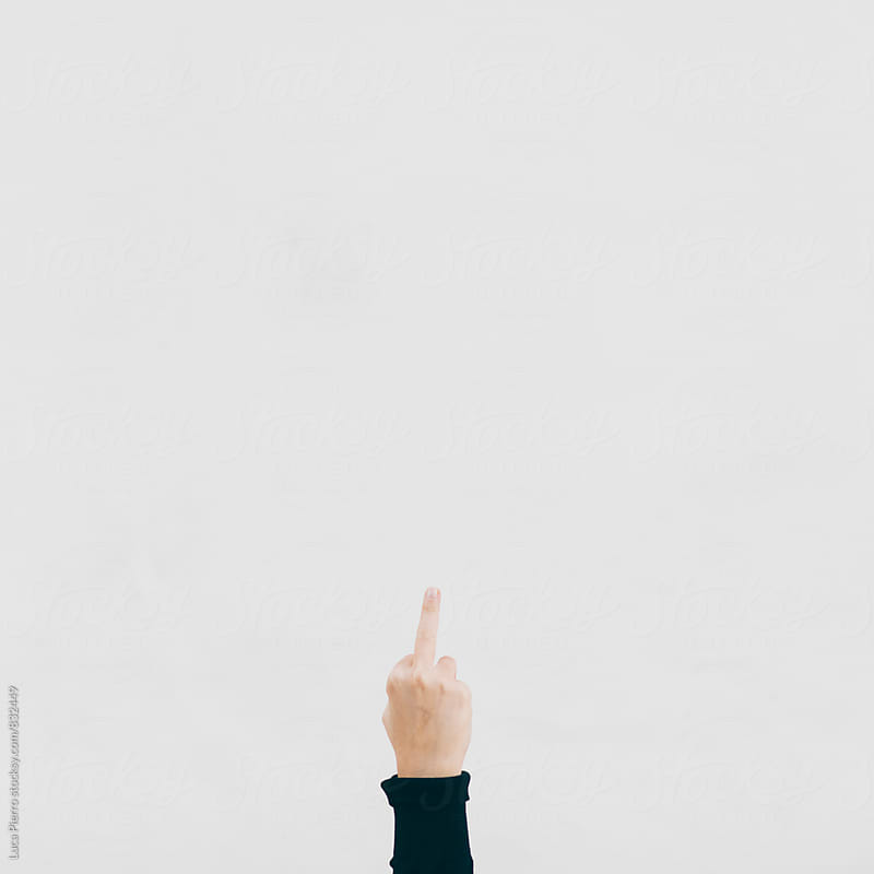 Middle finger against a white wall by Luca Pierro for Stocksy United