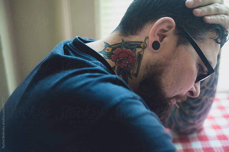 A handsome tattoo'd man in window light by Rachel Bellinsky for Stocksy United