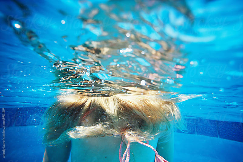 teen girl underwater with hair floating in water in pool by wendy laurel for Stocksy United