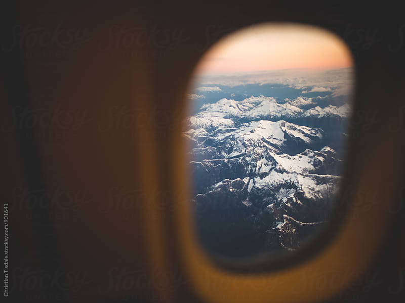 Sunrise lighting snowy mountain tops below from an airplane window by Christian Tisdale for Stocksy United
