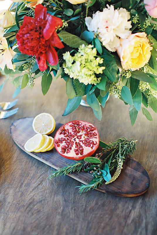 Cut up fruit and flowers on table by Daniel Kim Photography for Stocksy United