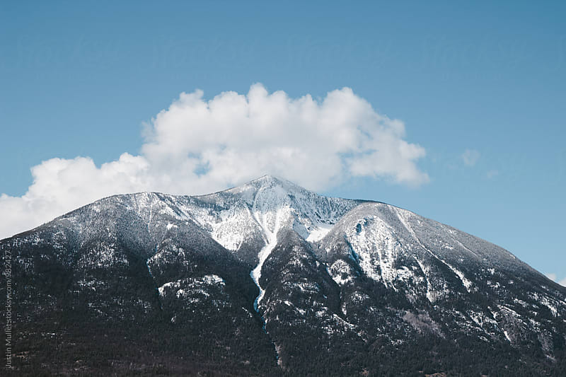 Cloud over snow covered mountain peak by Justin Mullet for Stocksy United