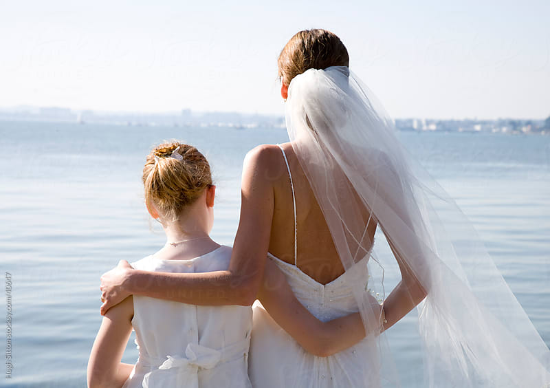 Bride with Flower Girl, standing by the sea. by Hugh Sitton for Stocksy United