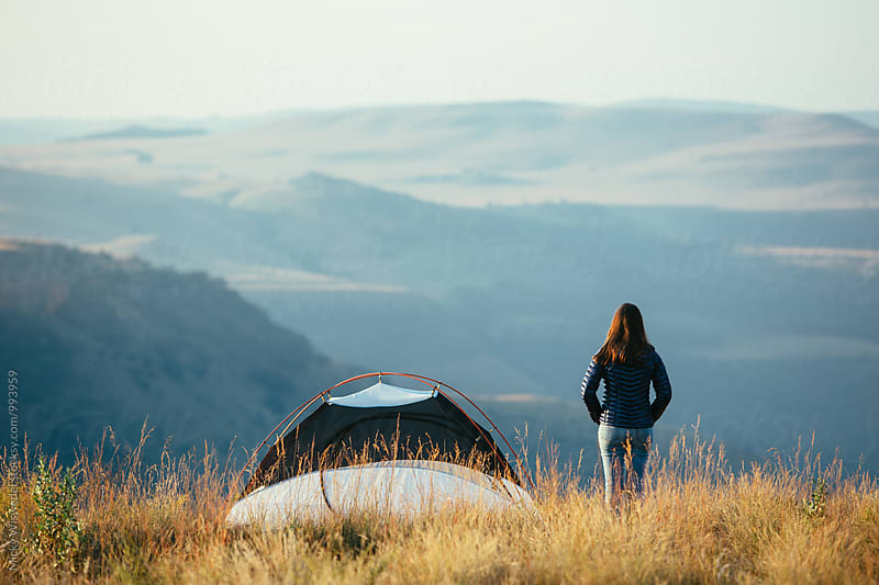 Hiker standing outside her summit camp tent overlooking a scenic valley at sunset by Micky Wiswedel for Stocksy United