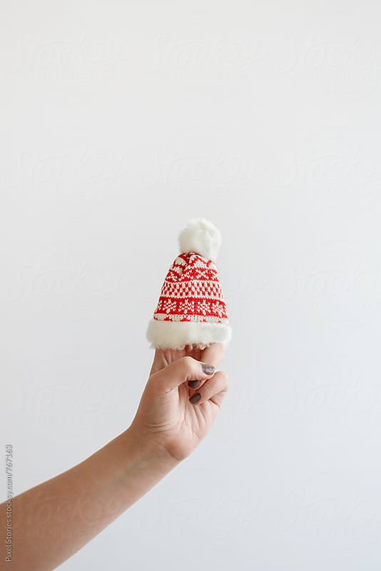 Hand holding tiny Santa's hat  by Pixel Stories for Stocksy United
