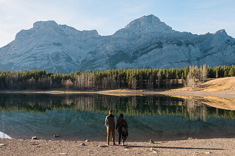 A young man & woman stand holding hands while looking at the mountain reflection on a pond. by Riley Joseph for Stocksy United