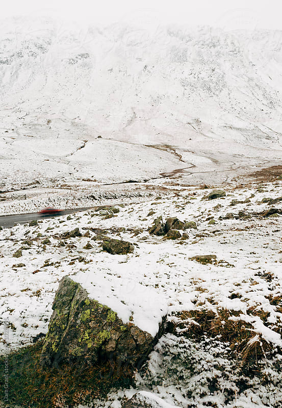 Vehicles driving on a mountain road in snow. Cumbria, UK. by Liam Grant for Stocksy United