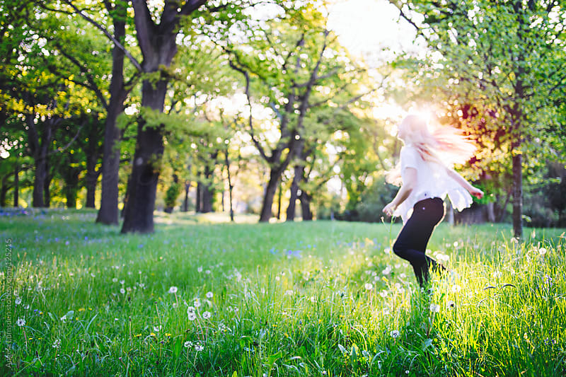 Girl running through a field of dandelions in evening sun by Angela Lumsden for Stocksy United