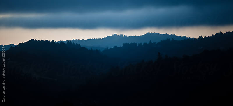 Dark and cloudy skyline - layers of mountains by Carolyn Lagattuta for Stocksy United