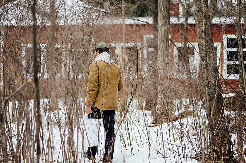 man carrying buckets of maple sap through woods by Deirdre Malfatto for Stocksy United