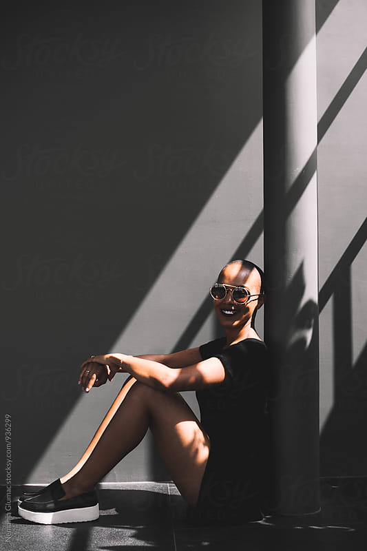 Young African American Woman Sitting in a Shadow by Nemanja Glumac for Stocksy United
