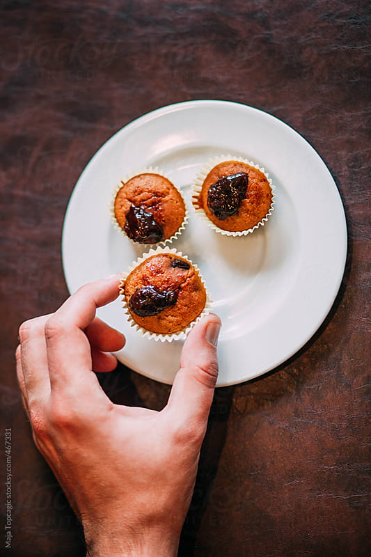 Male hand takes a fresh healthy homemade muffins with plum jam by Maja Topcagic for Stocksy United