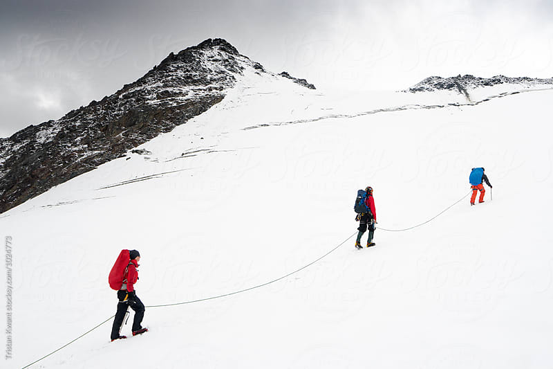 Three climbers walking with rope on a mountain by Tristan Kwant for Stocksy United