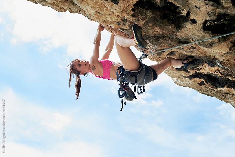 Sportswoman climbing the cliff by Guille Faingold for Stocksy United