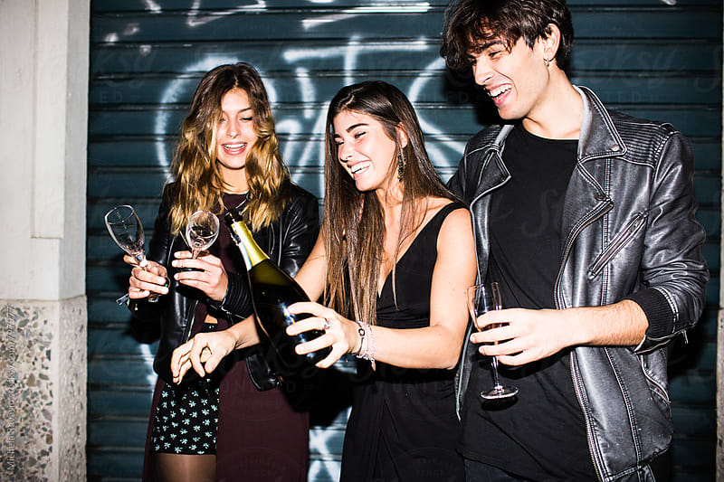 Group of friends celebrating together with champagne by michela ravasio for Stocksy United