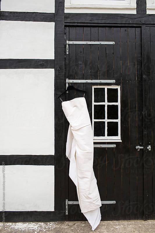 Wedding dress hanging on a barn door by Ann-Sophie Fjelloe-Jensen for Stocksy United