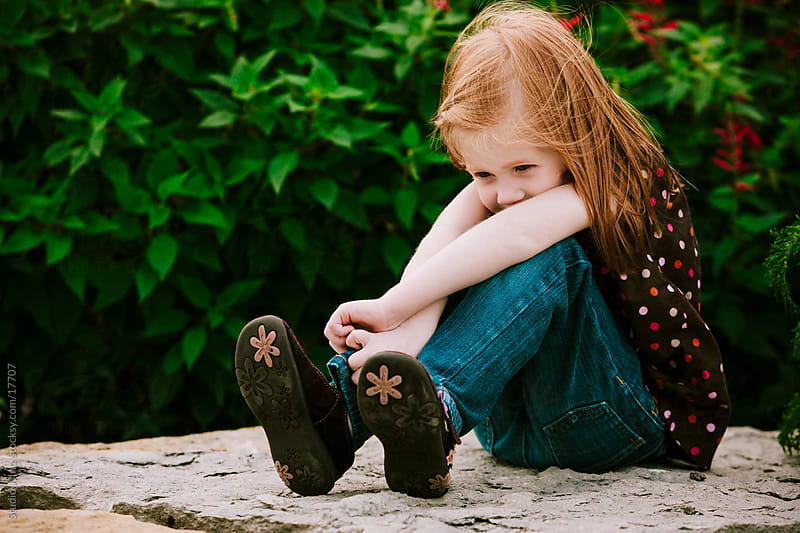 Little Redhead Girl Hugging Knees Outside by Jani Bryson for Stocksy United