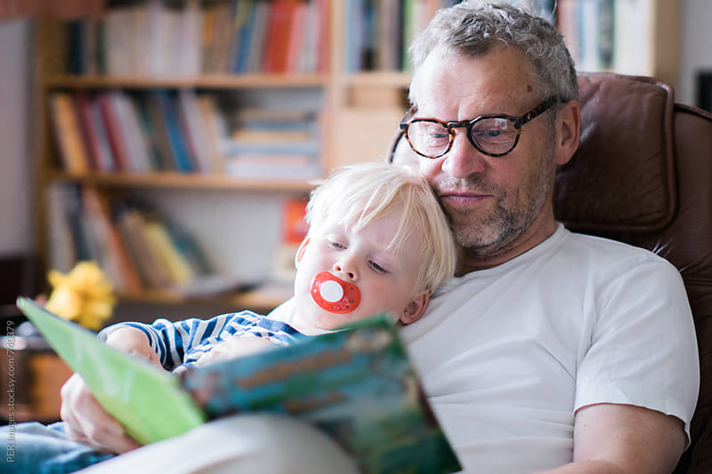 Grandfather reading a bed time story for a tired grandchild by Per Swantesson for Stocksy United
