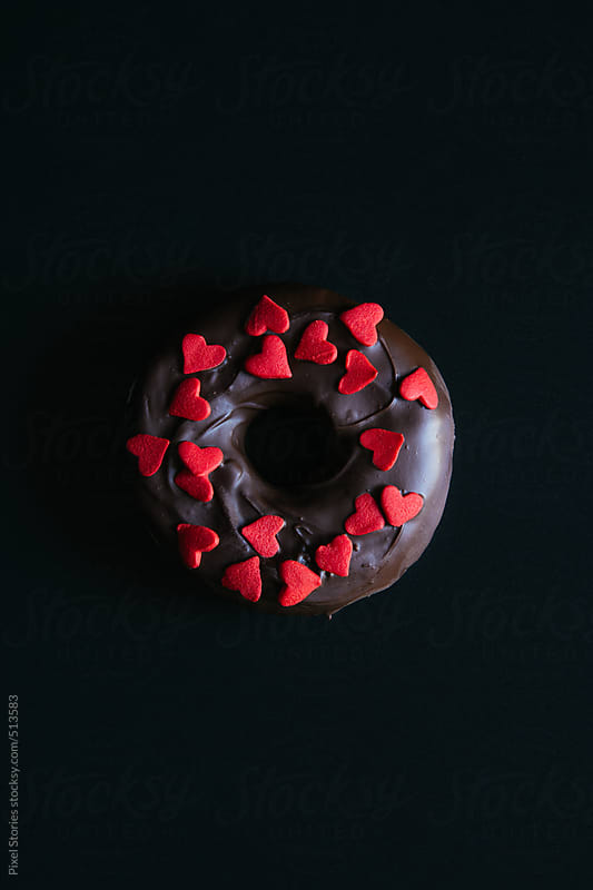 Chocolate donut with red sugar hearts by Pixel Stories for Stocksy United