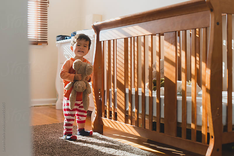 Happy toddler playing in room by Lauren Naefe for Stocksy United
