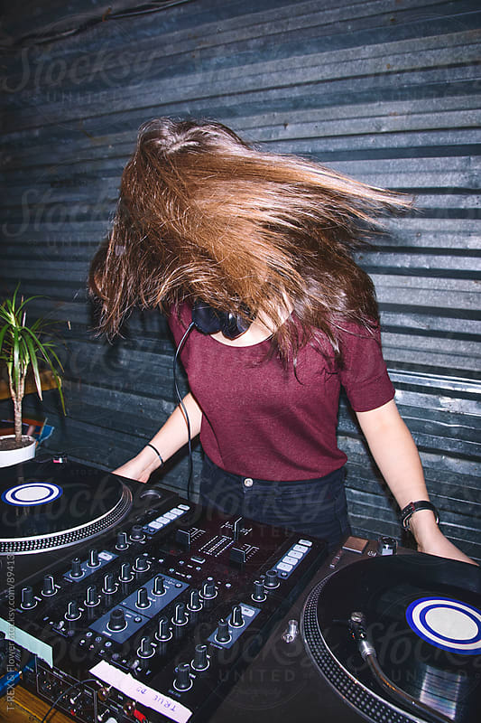 Young female DJ having fun at DJ board by T-REX & Flower for Stocksy United