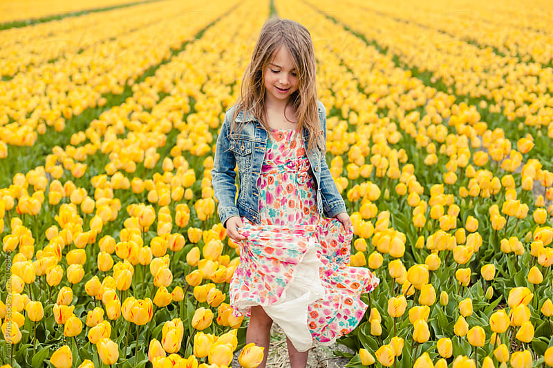 Little girl in a flower dress standing in a yellow tulip field