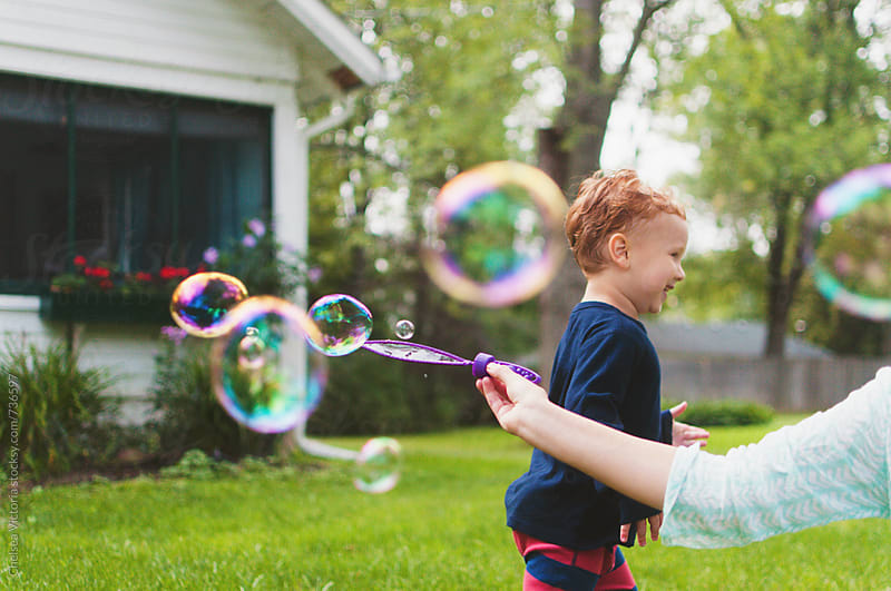 A mother and her son play with bubbles by Chelsea Victoria for Stocksy United