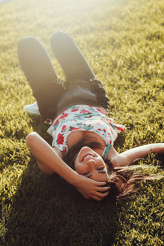 Girl smiling lying down on meadow upside down by paff for Stocksy United