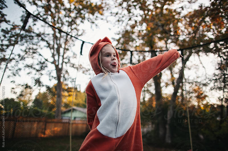 Cute girl in fox costume jumping on trampoline by Rob and Julia Campbell for Stocksy United