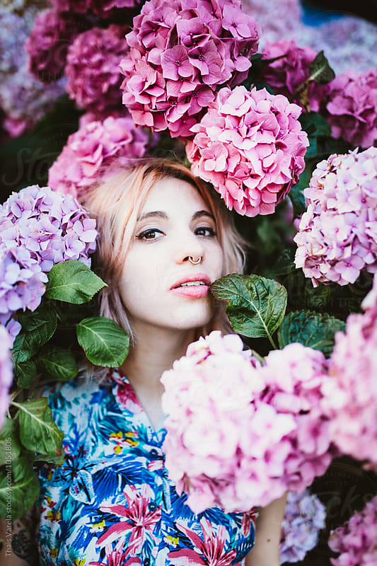 woman between pale hydrangeas by Thais Ramos Varela for Stocksy United