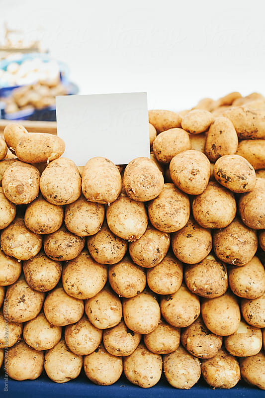 Potatoes on stall with an empty signboard by Borislav Zhuykov for Stocksy United