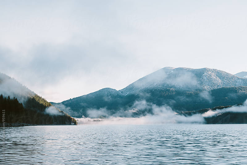 Thick fog burning off the shoreline of a mountain lake.  by Justin Mullet for Stocksy United