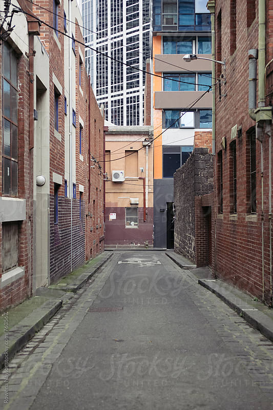 Old narrow laneway with new modern office buildings in background by Rowena Naylor for Stocksy United