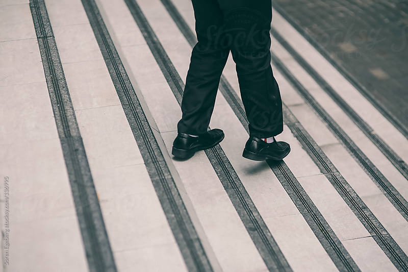 Closeup of mans black jeans and shoes walking down a stair case  by Soren Egeberg for Stocksy United