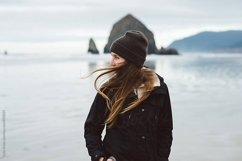 Young woman on windy Oregon coast by Kate Daigneault for Stocksy United