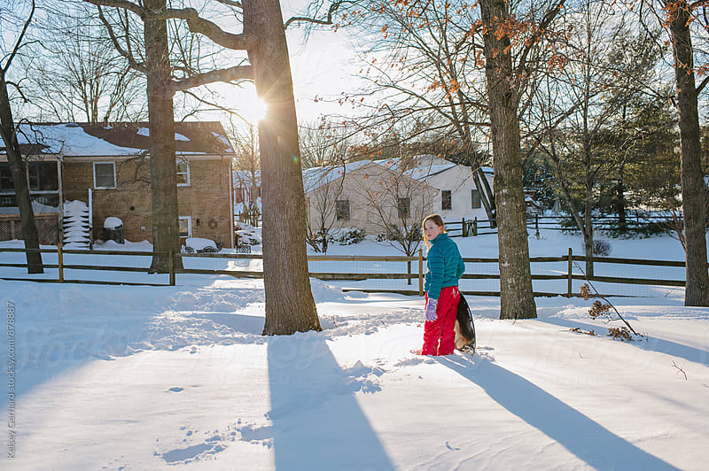 A teenage girl stands alone in a snowy landscape, in a patch of light. by Kelsey Gerhard for Stocksy United