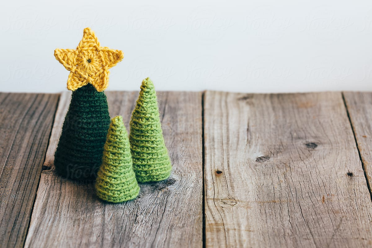 three little christmas trees on a rustic wood background with copyspace by jacqui miller for stocksy - Rustic Wood Christmas Tree