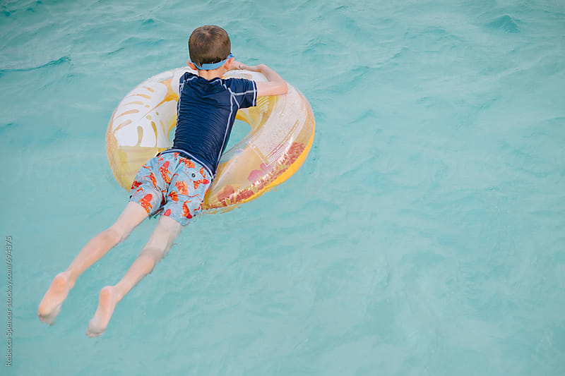 Taken from behind view of child floating on a ring in the pool by Rebecca Spencer for Stocksy United