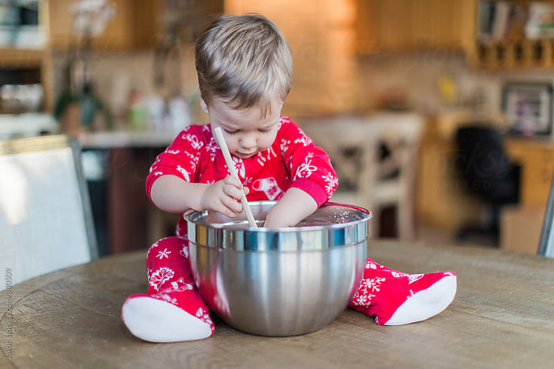 Cute young boy making pancakes in a onesie by Jakob for Stocksy United