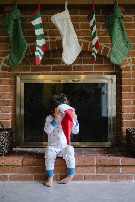 boy in pajamas peeks into Santa hat in front of fireplace by Tara Romasanta for Stocksy United