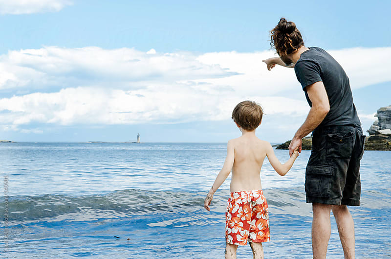 Boy and his dad stand together by the ocean by Cara Dolan for Stocksy United