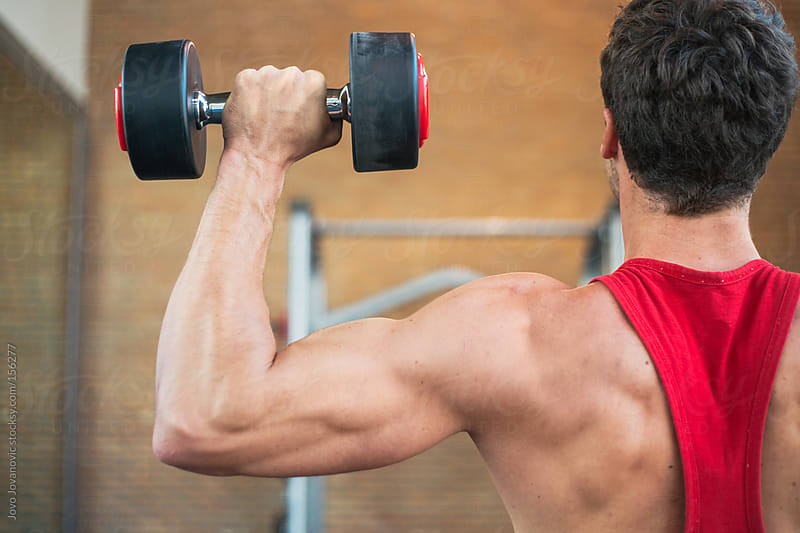 Close up of young man lifting weights by Jovo Jovanovic for Stocksy United