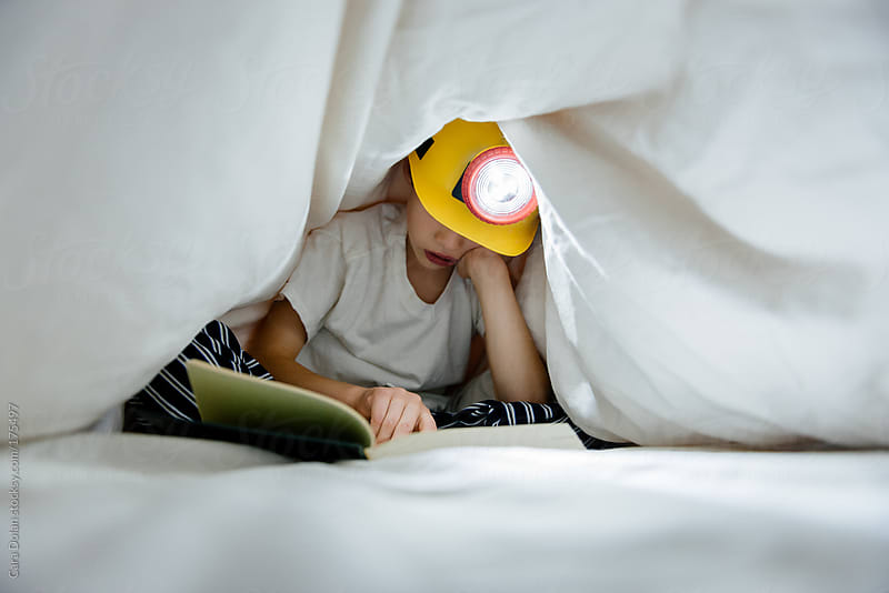 Child hides under bed covers, reading a book by the light of a headlamp by Cara Dolan for Stocksy United