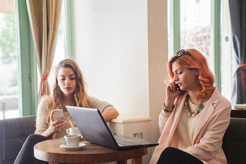 Busy Women talking on Phone During Coffee Break by Audrey Shtecinjo for Stocksy United