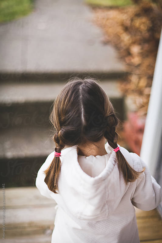 Back view of little girl with braids by Amanda Worrall for Stocksy United