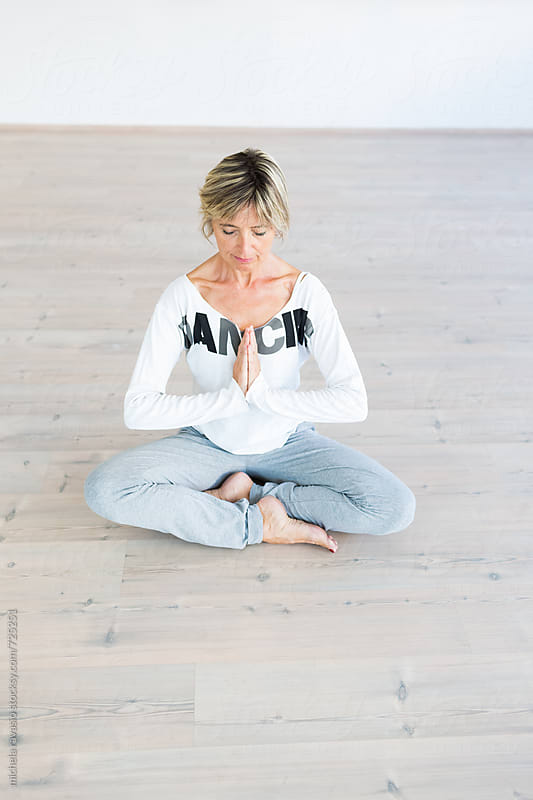 Mature woman doing meditation indoors by michela ravasio for Stocksy United